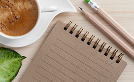 A note pad and a cup of coffee